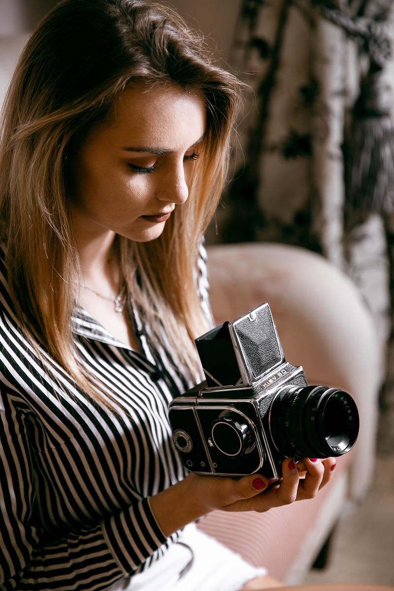 Spogląda w wizjer aparatu fotograficznego Kiev 80 u fotograf Biłgoraj.