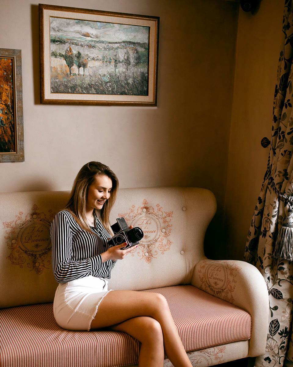 Oparta siedzi na kanapie i uśmiecha się na myśl o sesja kobieca, którą zobaczyła w starym aparacie.