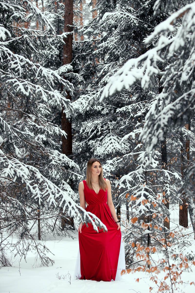 Las obsypany śniegiem a po środku stoi dziewczyna na sesja kobieca w plenerze.