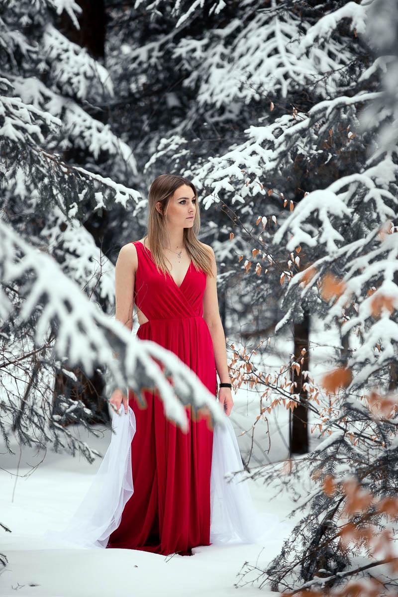 Dziewczyna w czerwonej sukience w lesie. Drzewa obsypane śniegiem na sesja zdjęciowa zimowa.