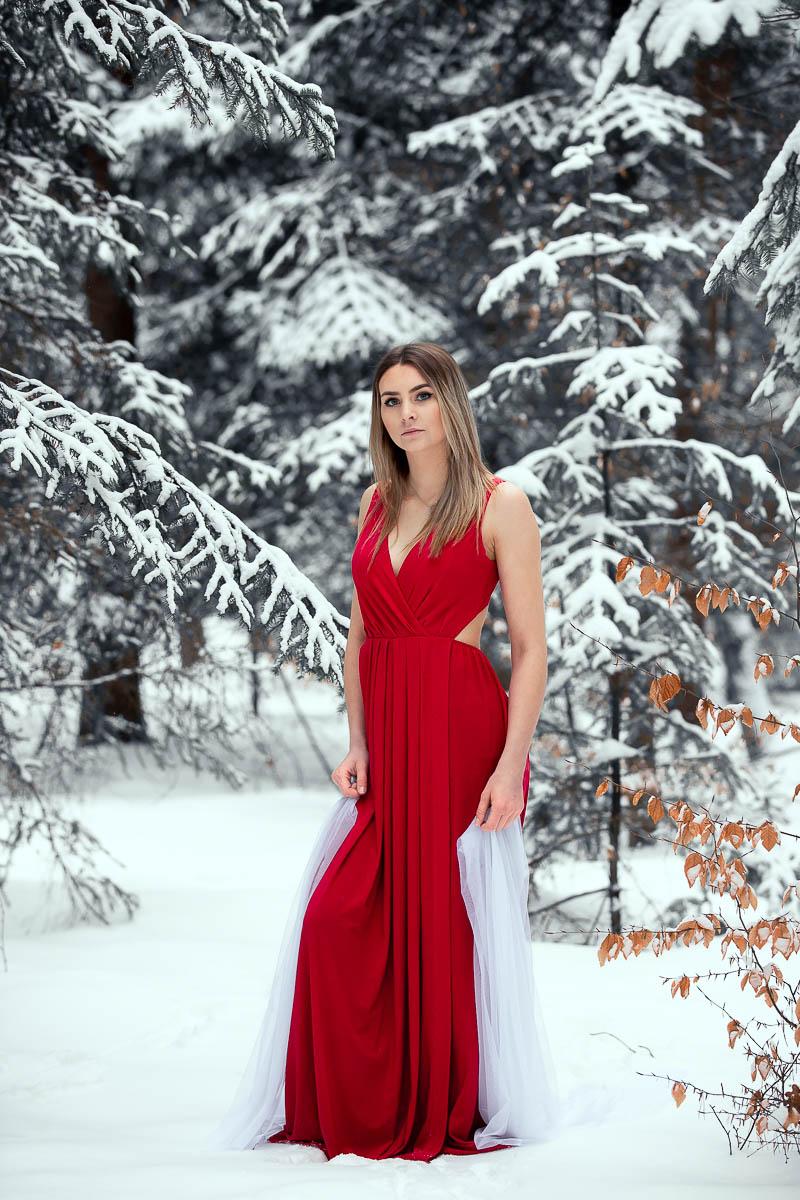 Dziewczyna w czerwonej sukience jak na bal na sesja kobieca patrzy się przed siebie.