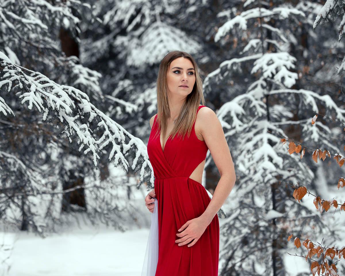 Dziewczyna w czerwonej sukience na sesja kobieca ogląda się za siebie.