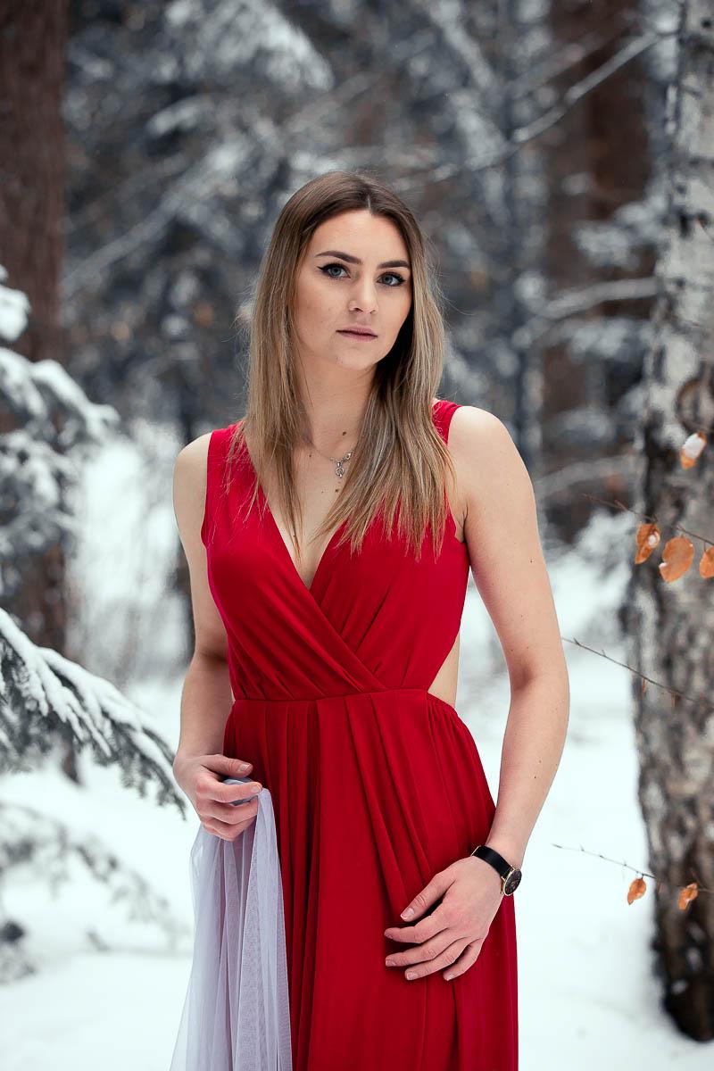 Dziewczyna z długimi blond włosami na sesja w lesie. Trzyma w ręku biały welon.