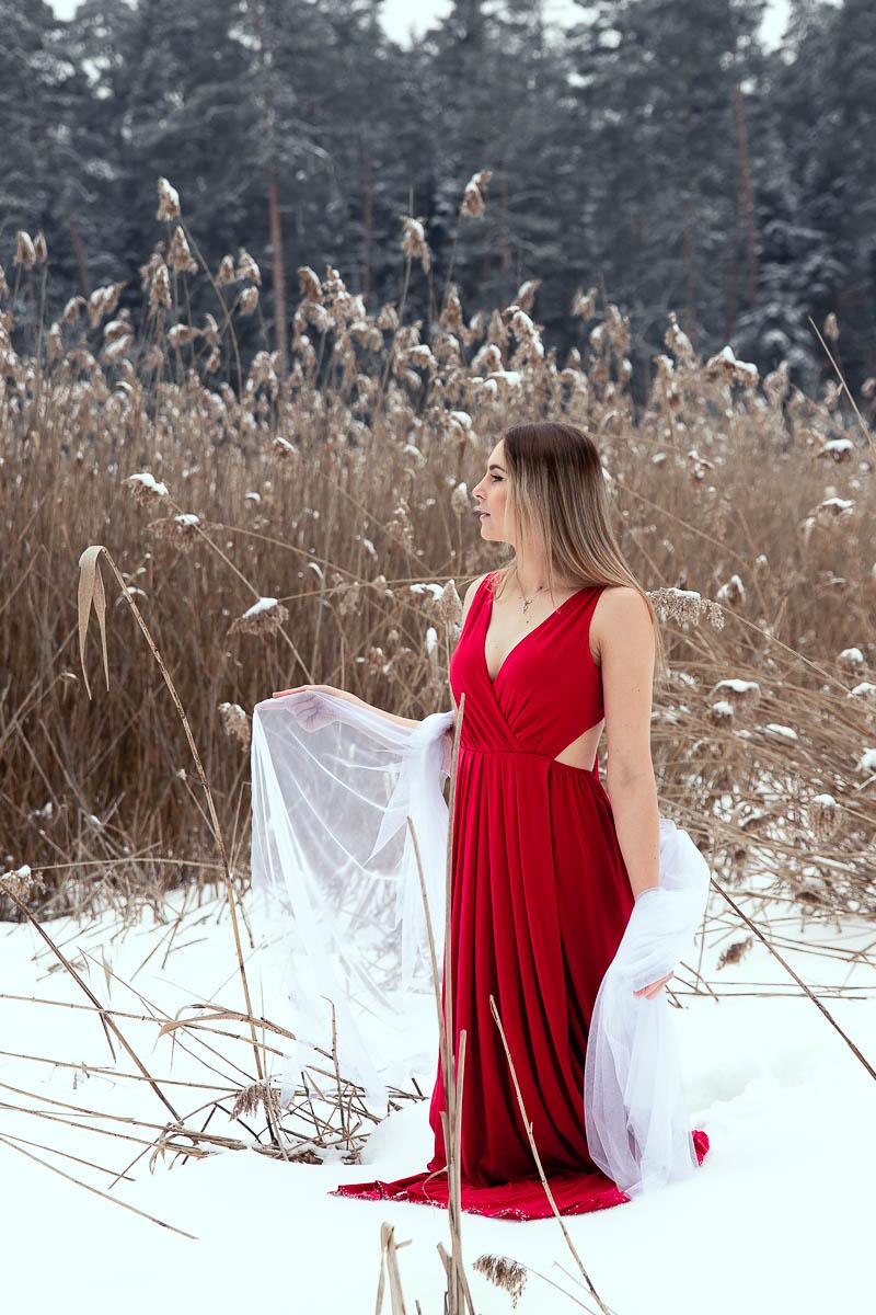 Stoi na brzegu jeziora jak na sesja ślubna w lesie na ramionach biały welon.