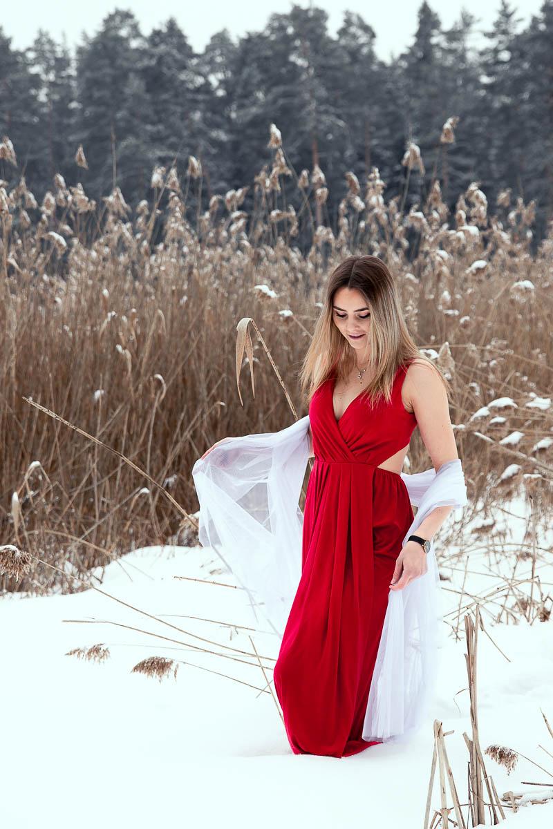 Uśmiechnięta spogląda na czerwoną sukienkę na sesja kobieca.