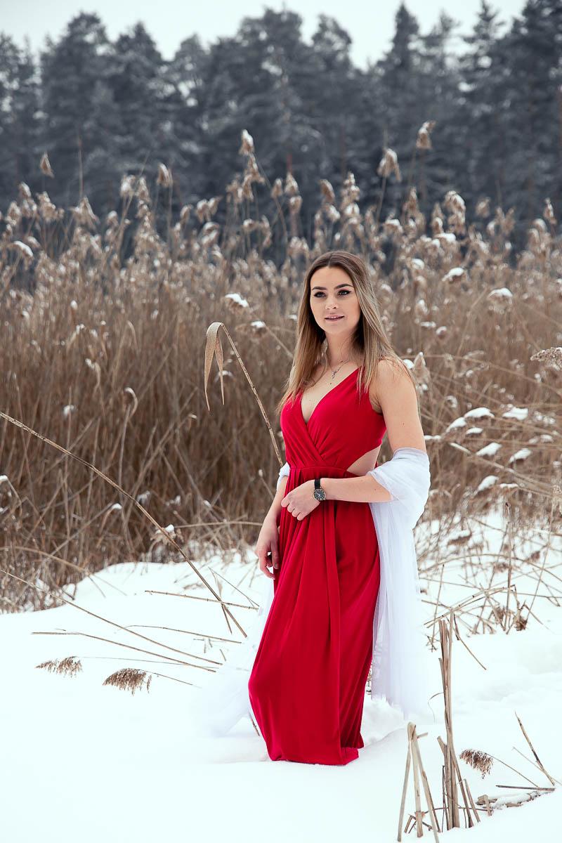 Dziewczyna w czerwonej sukience stoi na brzegu jeziora. Za nią trzciny i las na sesja zdjęciowa na prezent.
