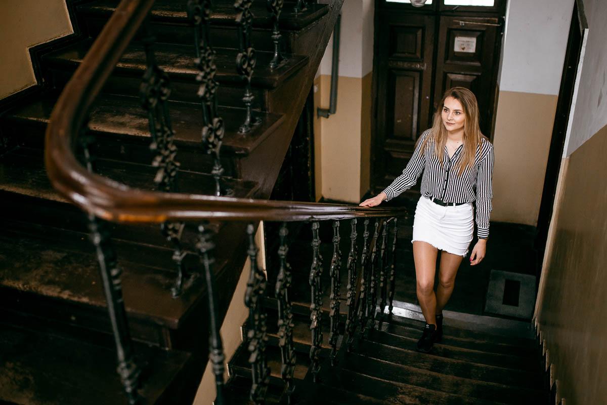 Dziewczyna pokazana od przodu wchodzi po drewnianych schodach w starej kamienicy na stare miasto w Zamościu.