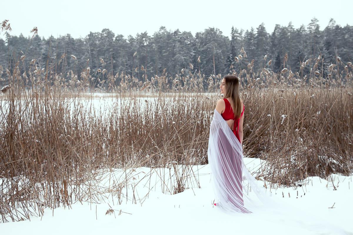 Zamyślona stoi na brzegu jeziora jak na profesjonalna sesja fotograficzna.