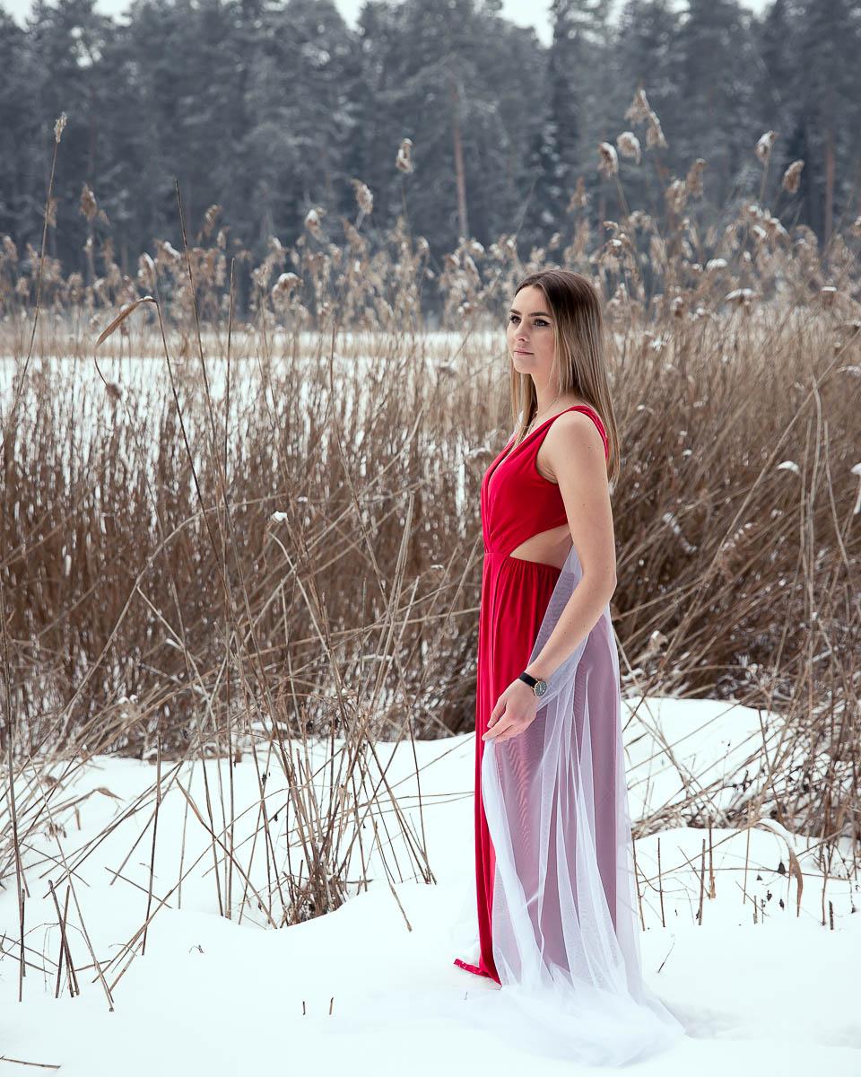 Dziewczyna w czerwonej sukience z długimi blond włosami na profesjonalna sesja kobieca.