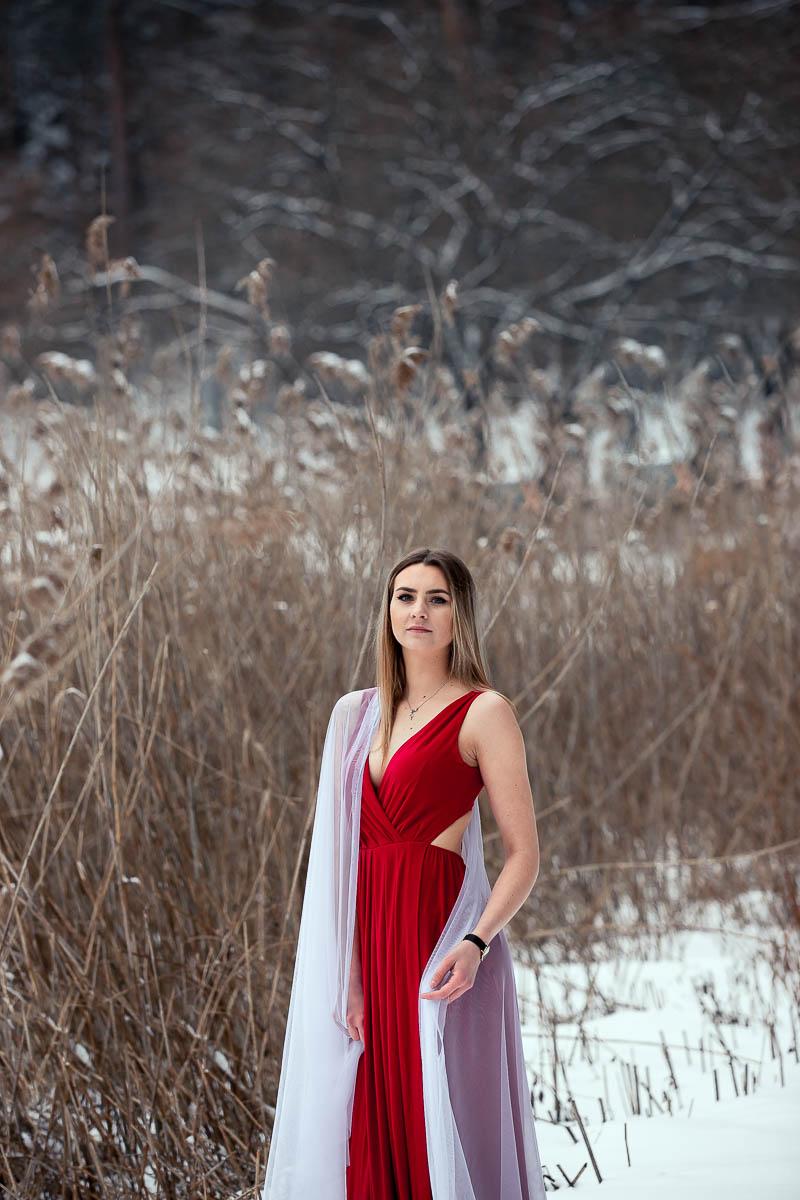 Uśmiechnięta dziewczyna w czerwonej sukience z białym welonem na ramieniu na profesjonalna sesja ślubna.