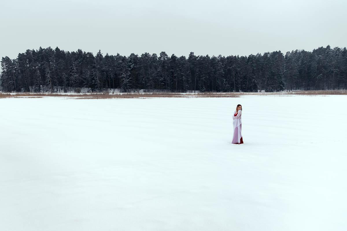 Dziewczyna owinięta w welon stoi na środku zamarzniętego jeziora w Zwierzyńcu nad stawy echo.
