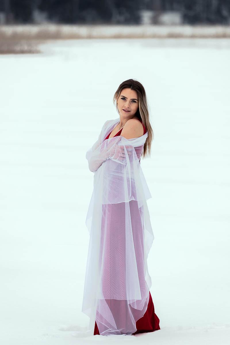Zmarznięta w suknia stoi na środku jeziora wtulona w biały welon jak na sesja ślubna Lublin.