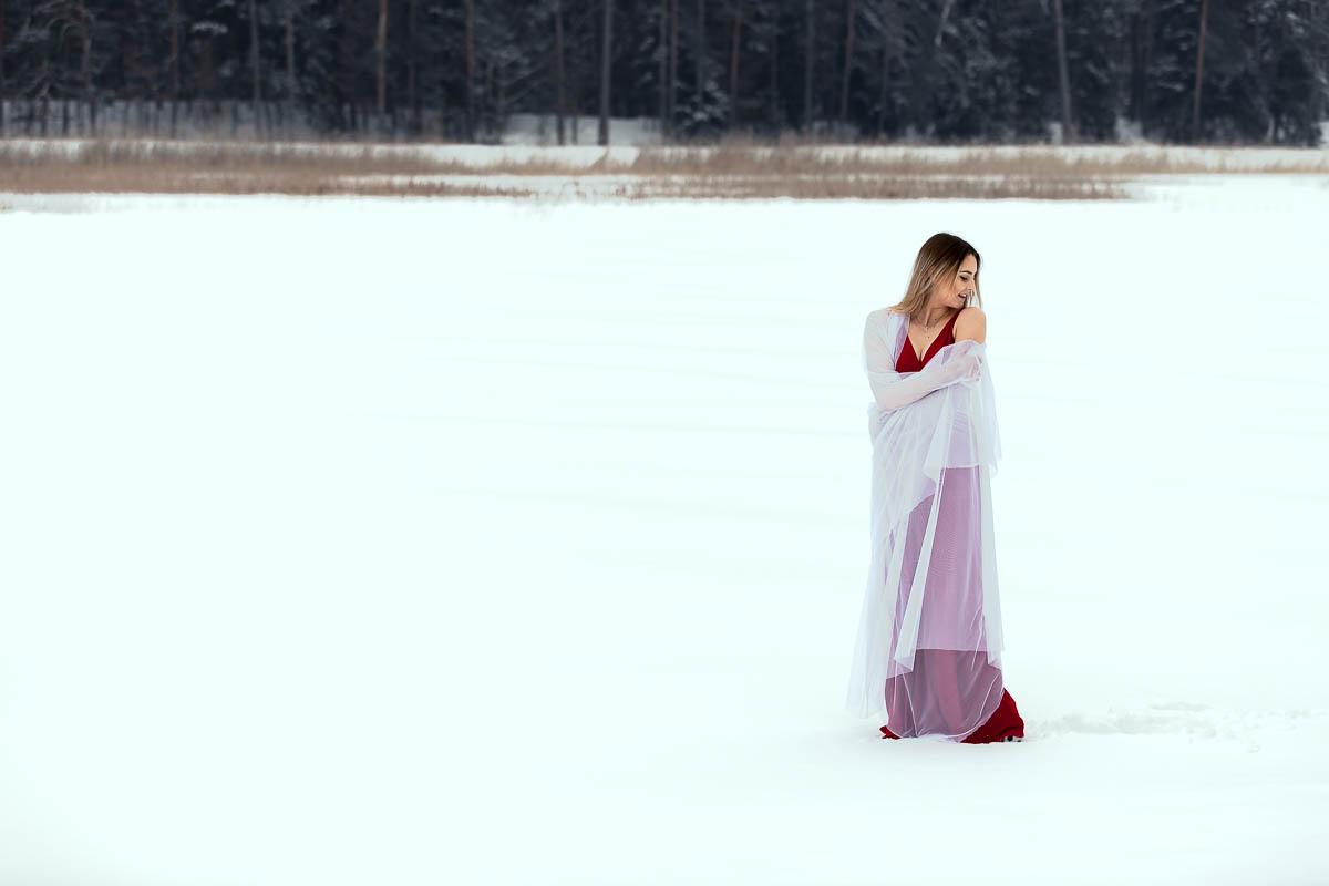 Spogląda za siebie przez ramię owinięta w biały welon jak na sesja kobieca nad Stawy Echo w Zwierzyńcu.