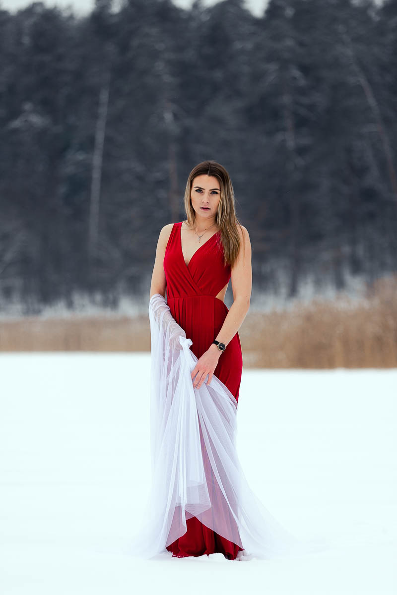 Dziewczyna w pięknej długiej czerwonej sukni stoi na jeziorze. Patrzy na Stawy Echo w Zwierzyńcu jak na sesja kobieca zimowa.