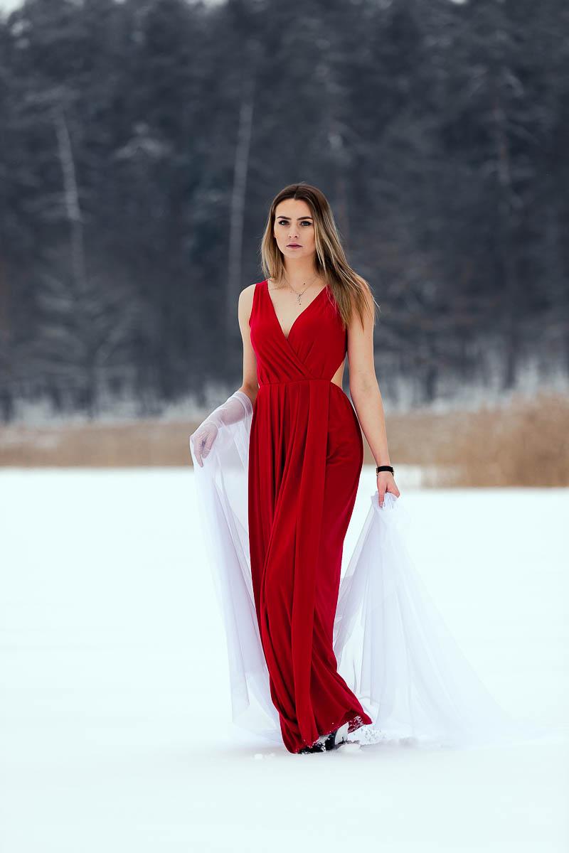 Dziewczyna w pięknej długiej czerwonej sukni idzie po jeziorze jak na profesjonalna sesja kobieca.