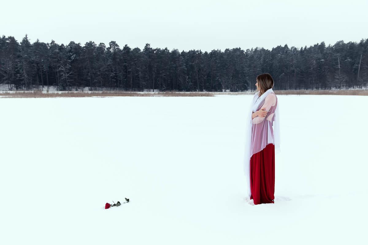 Stoi na jeziorze i patrzy w dal. Obok leży róża. Zdjęcie zrobione przez fotograf ślubny Lublin.