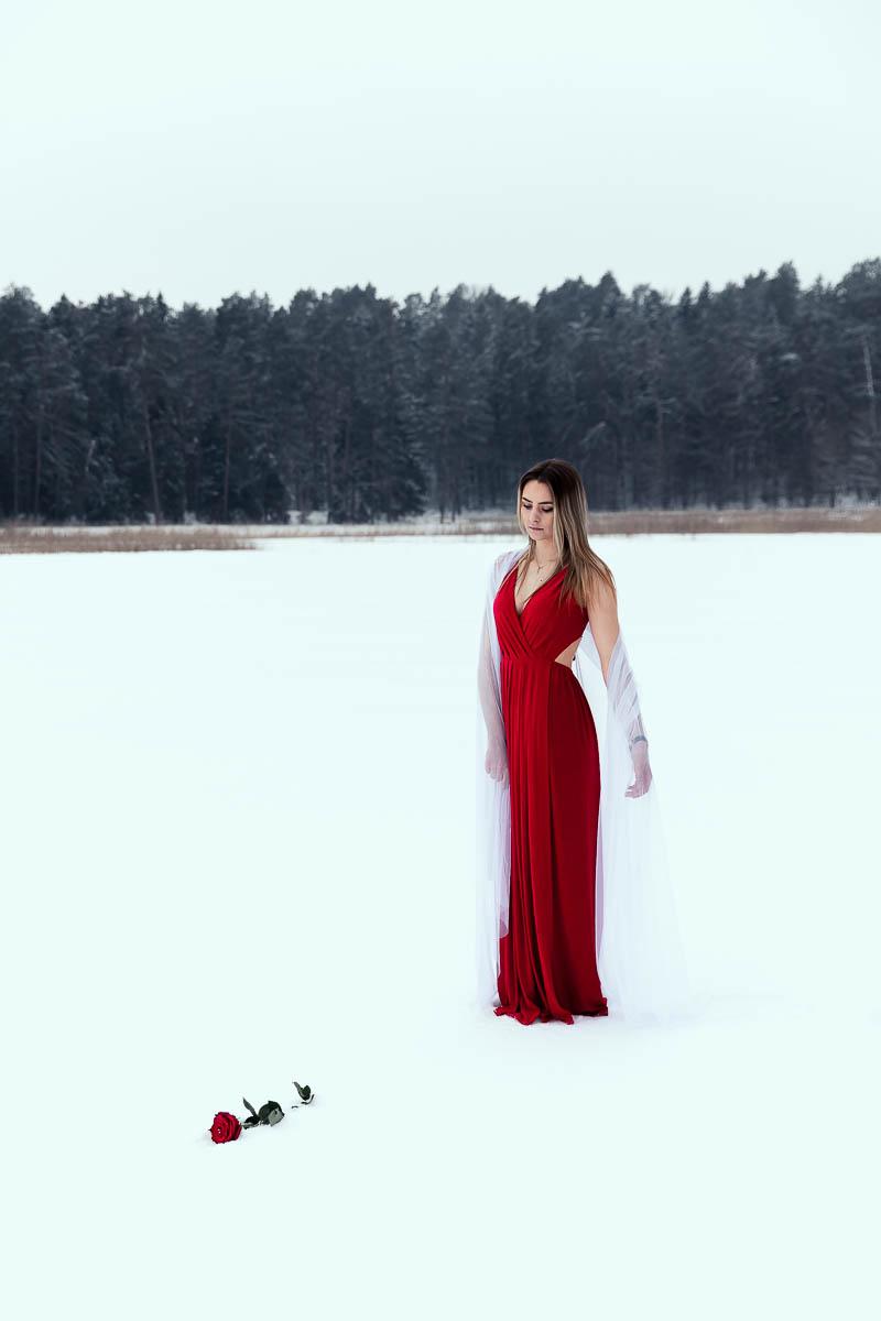 Stoi przyglądając się na różę. Na ramionach pięknie opada biały welon jak na sesja ślubna w lesie.