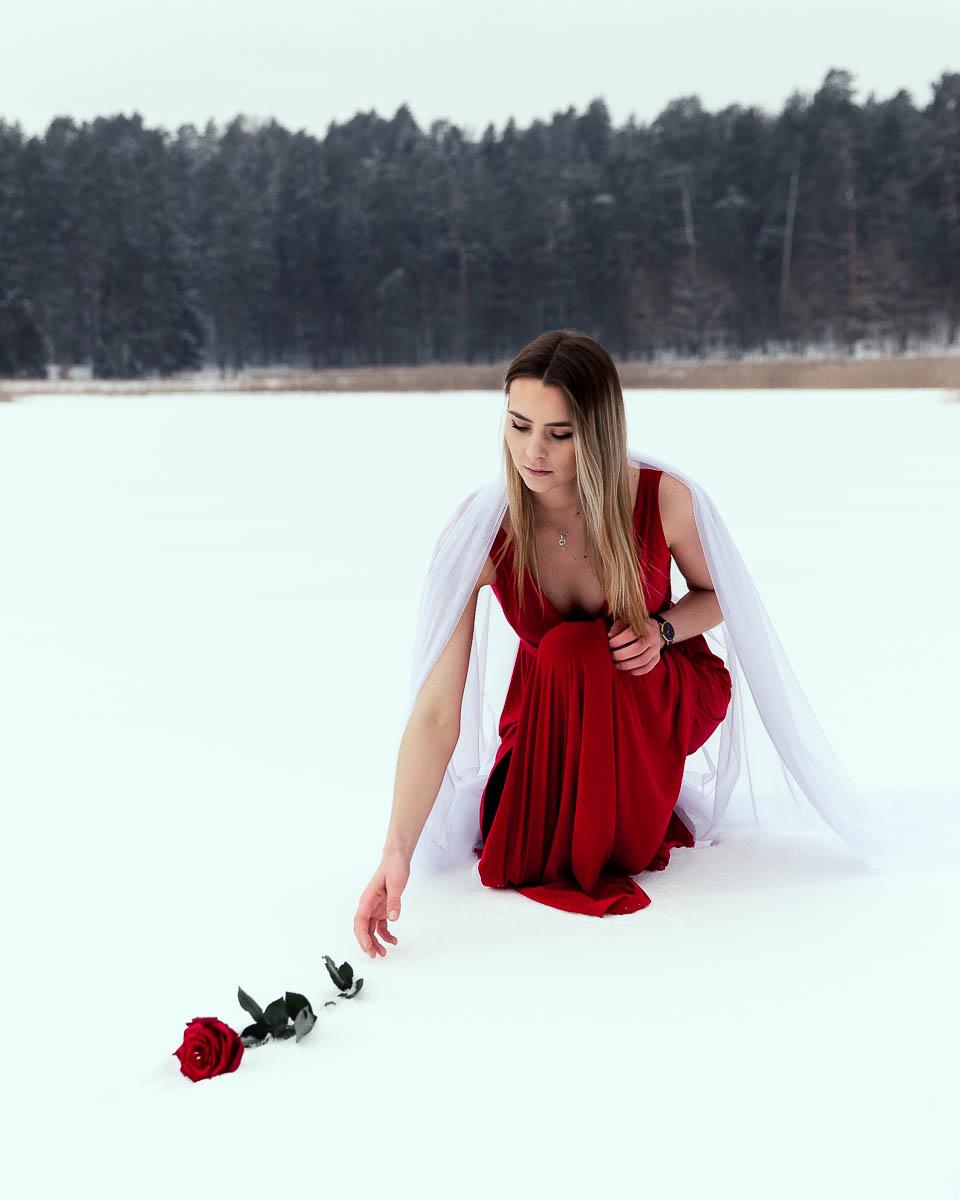 Wyciąga rękę po różę. Czerwona sukienka pięknie opada na Stawy Echo w Zwierzyńcu.