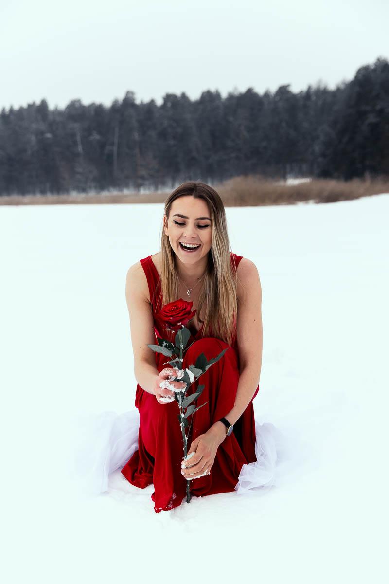 Roześmiana trzyma różę w rękach. Na rękach ma przyklejony śnieg jak na profesjonalna sesja kobieca.