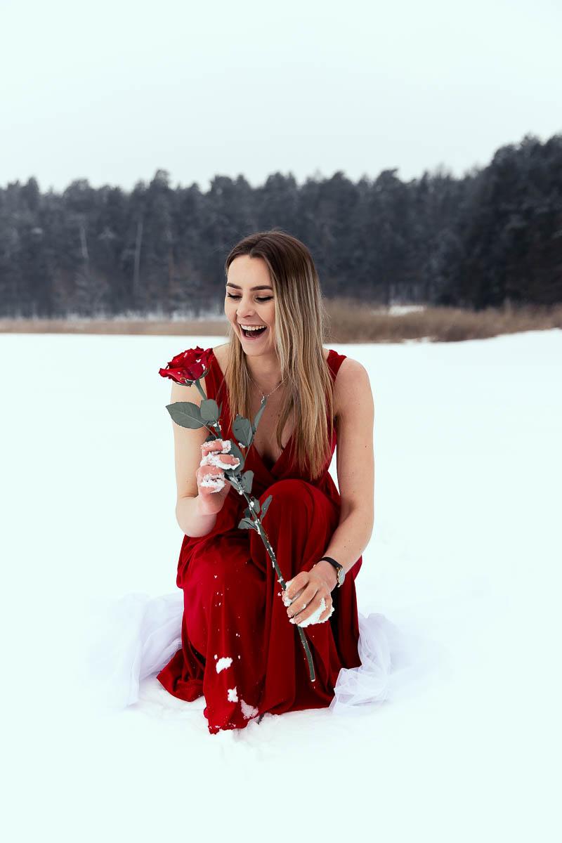 Roześmiana trzyma różę w rękach. Wygląda jak na sesja ślubna u fotograf ślubny Lublin.