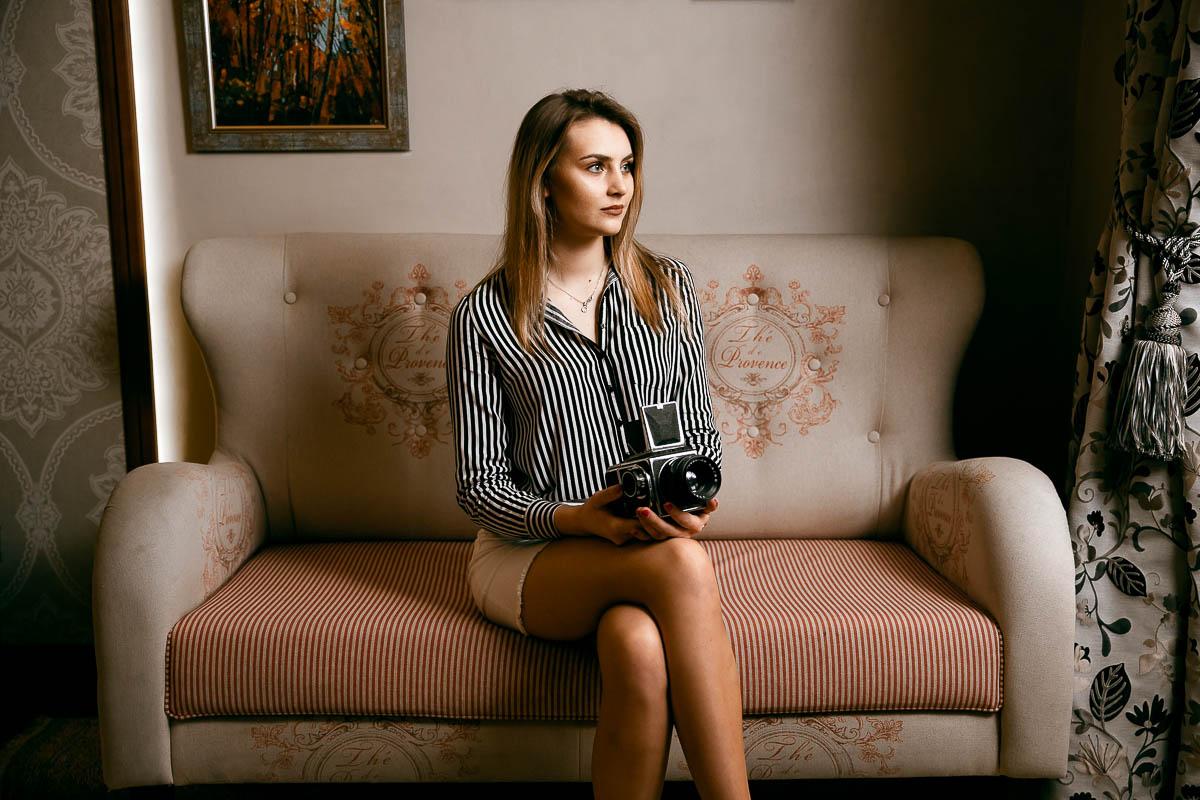 Zamyślona wpatruje się w okno, za którym jest fotograf ślubny Zamość.