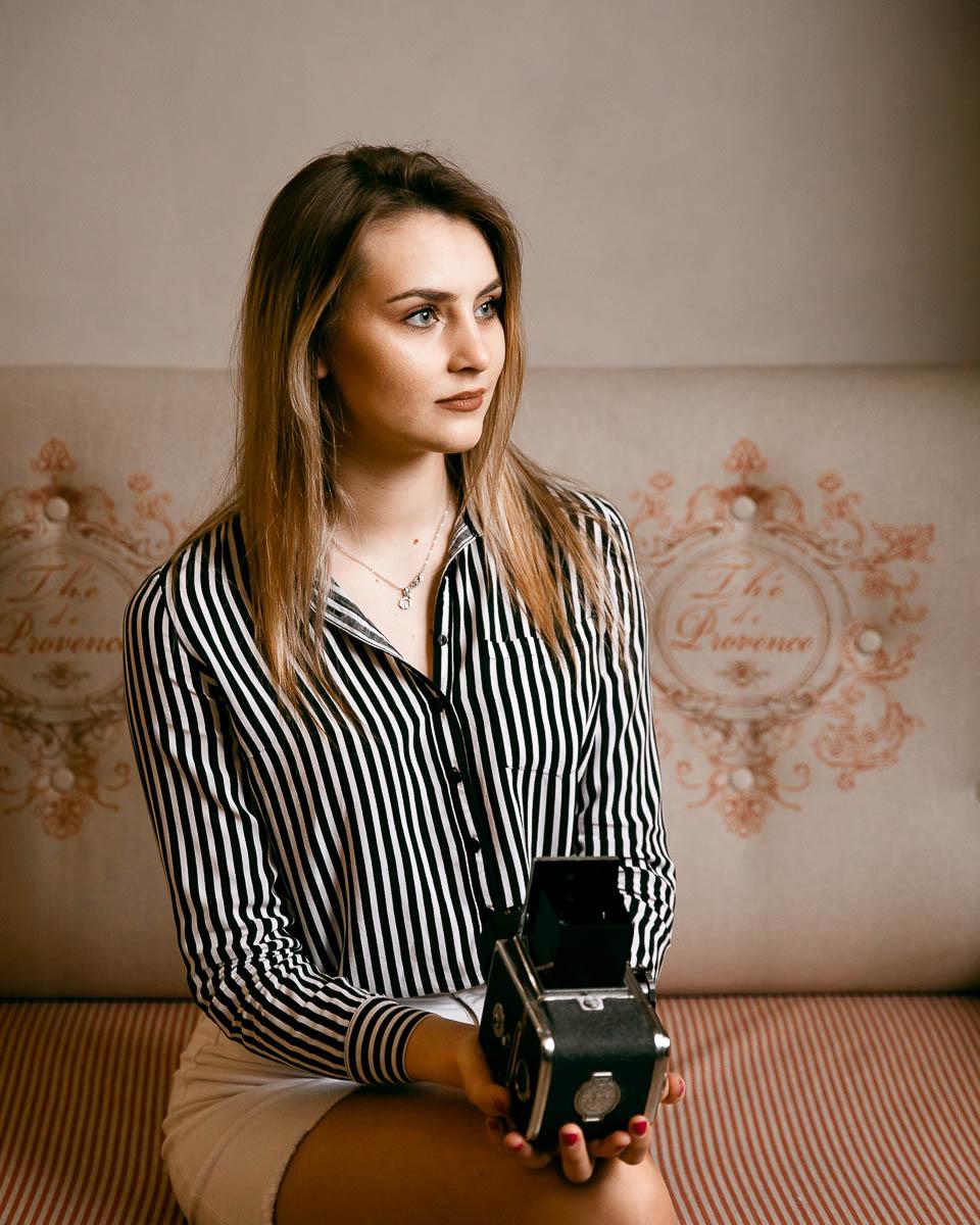 Siedzi na sofie, w ręku trzyma stary aparat Kiev 80. Włosy opadają jej na ramiona jak na sesja e domu.