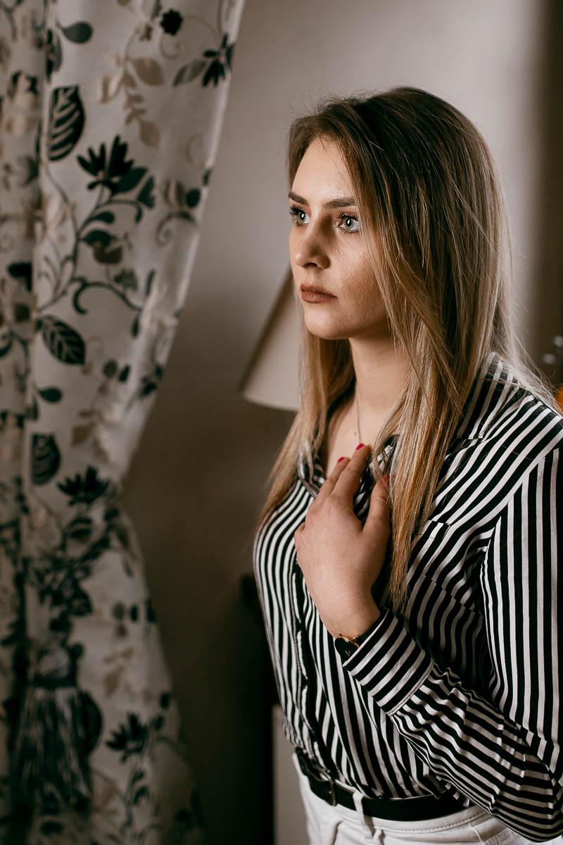 Zamyślona kładzie rękę na piersi jak na sesja sensualna Lublin.