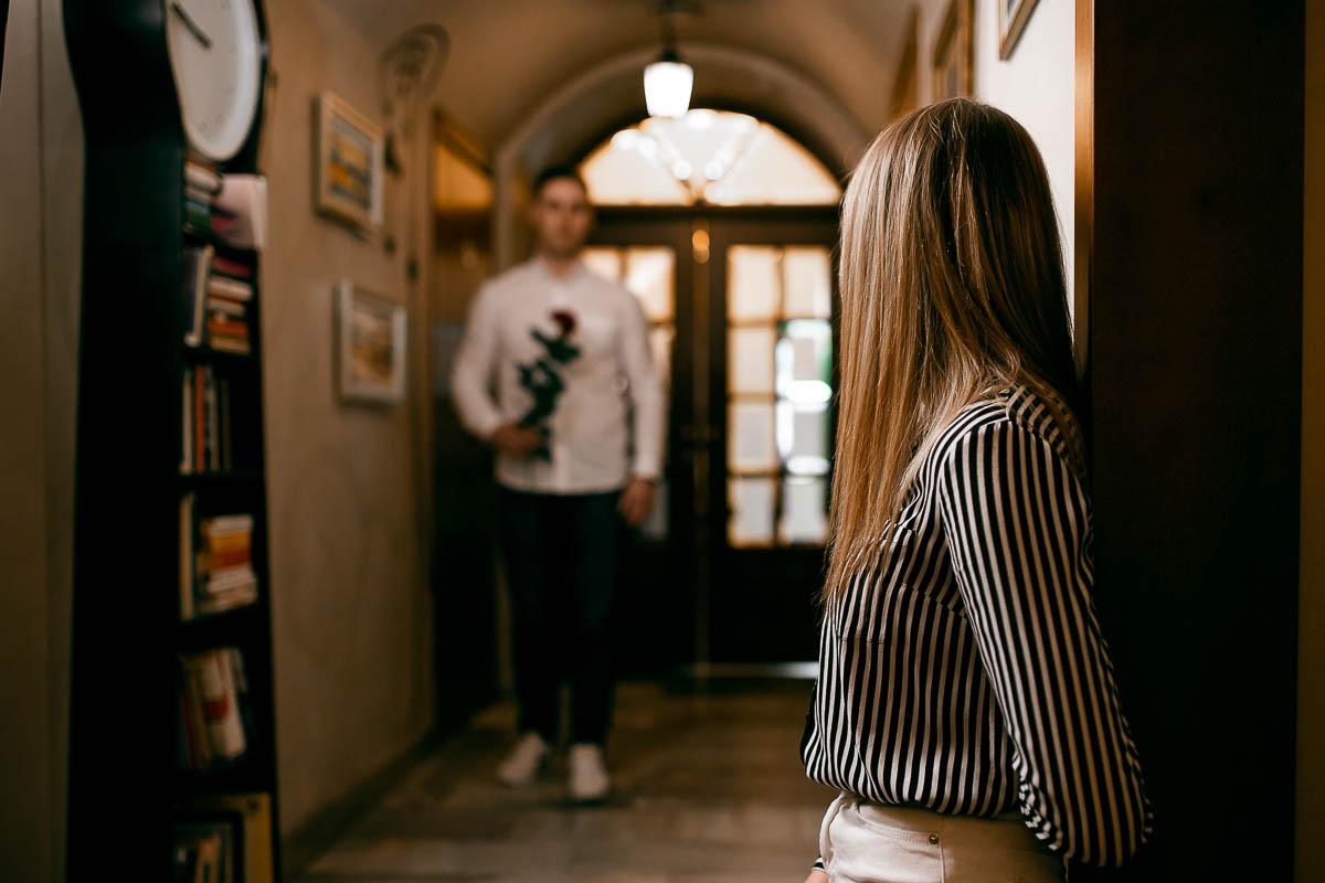 Chłopak stoi w głębi korytarza, w ręku trzyma różę. Obok stoi szafka z książkami a na ścianach wiszą obrazy z sesja kobieca.