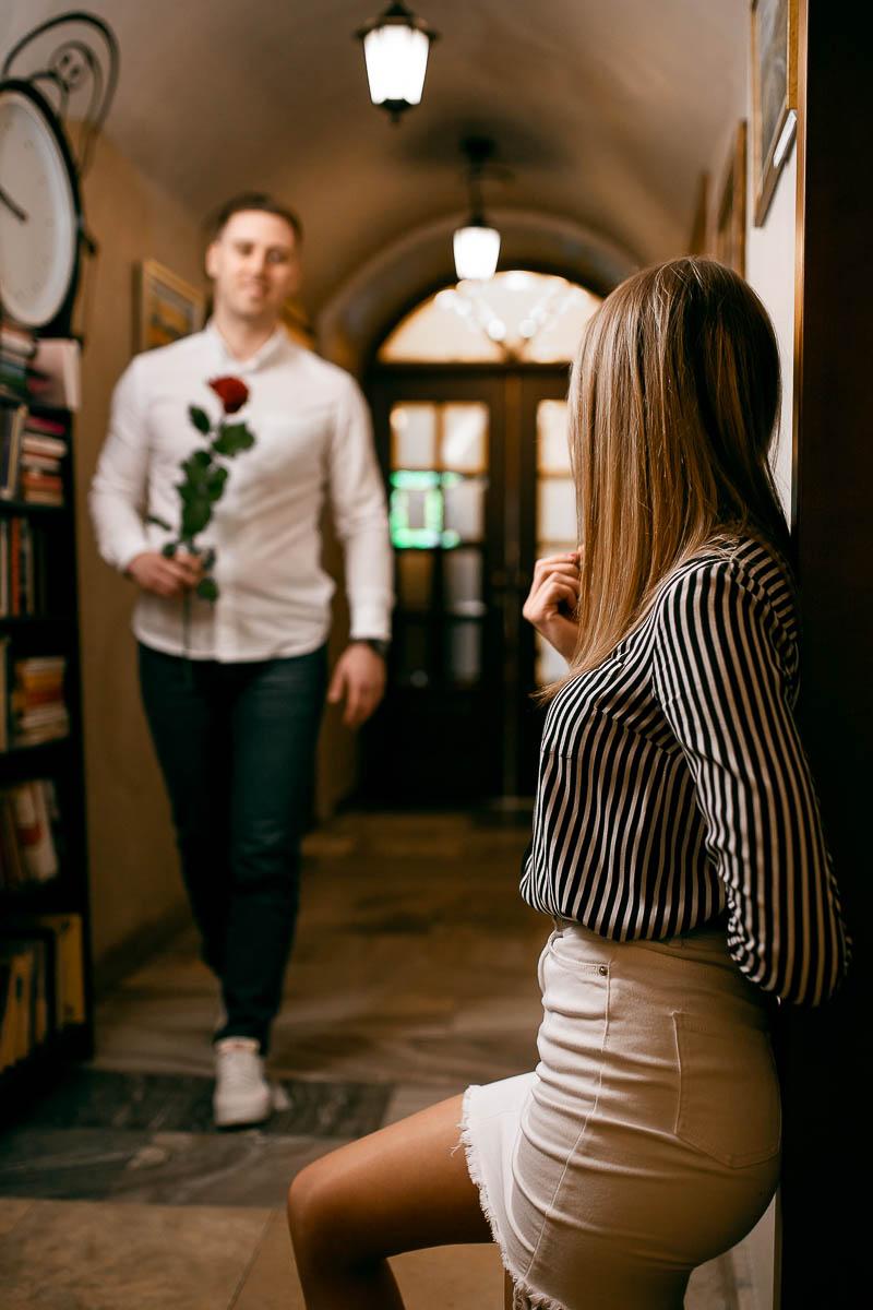 Oparta o ścianę patrzy w stronę chłopaka, który idzie do niej jak Pan Młody na sesja ślubna Lublin.