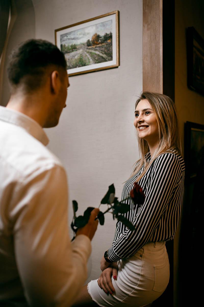 Patrzy roześmiana na chłopaka, który w ręku trzyma różę jak z bukiet ślubny panny młodej.