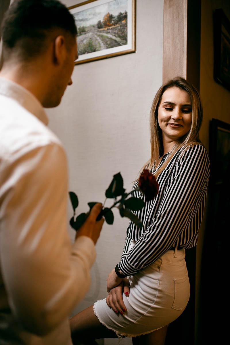 Chłopak stoi przed dziewczyną. Dziewczyna zawstydzona patrzy w bok na fotograf ślubny Lublin.