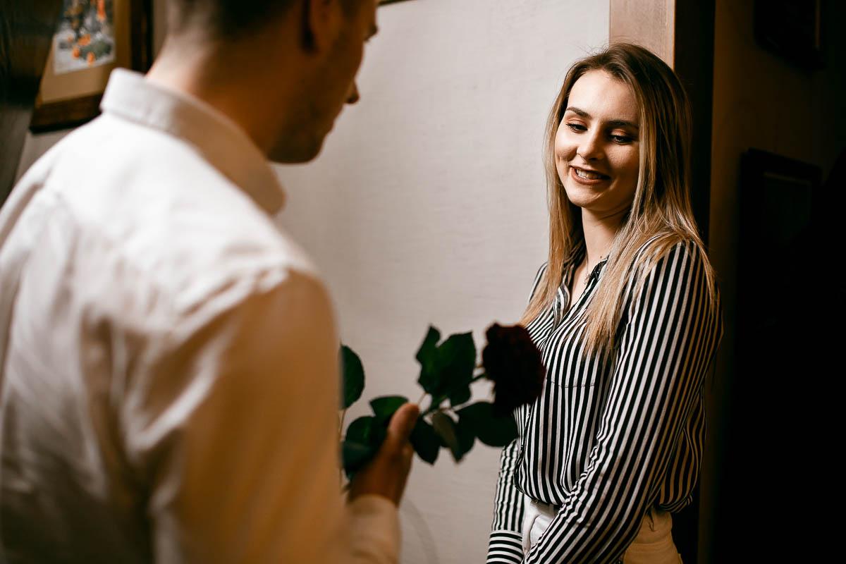 Uśmiechnięta patrzy na różę rozmawiając z chłopakiem o kobieca sesja fotograficzna.