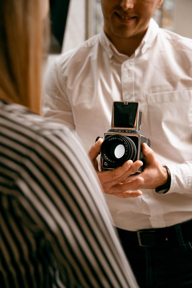 Ona stoi odwrócona tyłem, a no trzyma w ręku stary aparat fotograficzny na kliszę od fotograf Lublin.