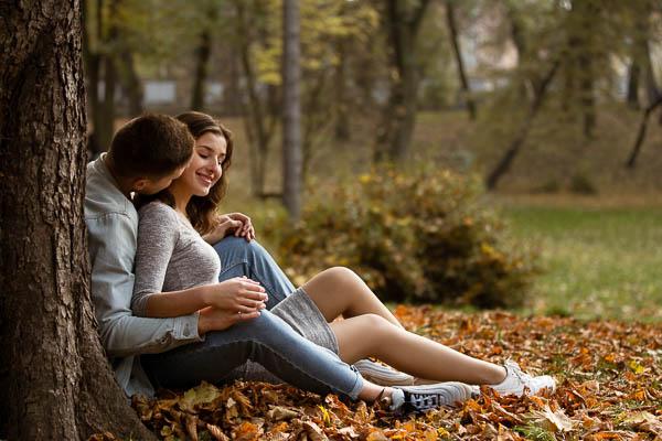 Zakochana para siedzi pod drzewem na jesiennych liściach