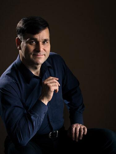 Portret siedzącego mężczyzny w studiu oświetlonego lampami