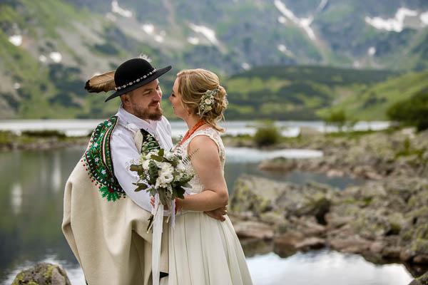 Pan Młody w stroju góralskim patrzy na Panią Młodą na tle górskiego jeziorka w Tatrach
