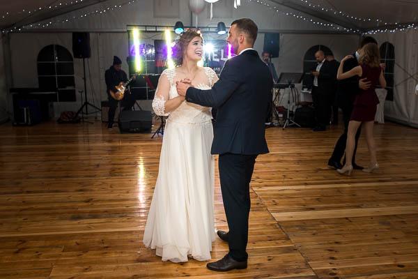 Pani Młoda w prostej sukni z Panem Młodym tańczą na parkiecie oświetleni kolorowymi światłami