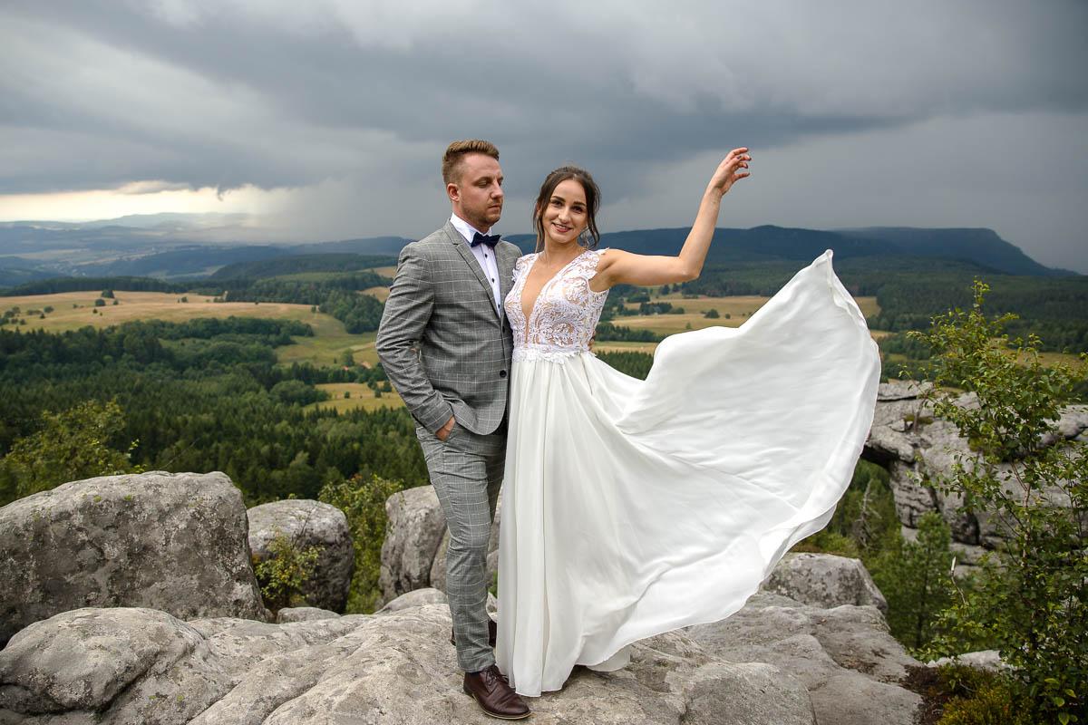 Pani Młoda stoi na skale z Panem Młodym podrzucając rąbek sukni ślubnej