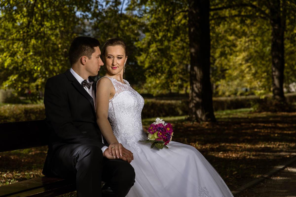 Panna Młoda siedzi w sukni ślubnej zdobionej koronką na ławce w parku oparta o Pana Młodego
