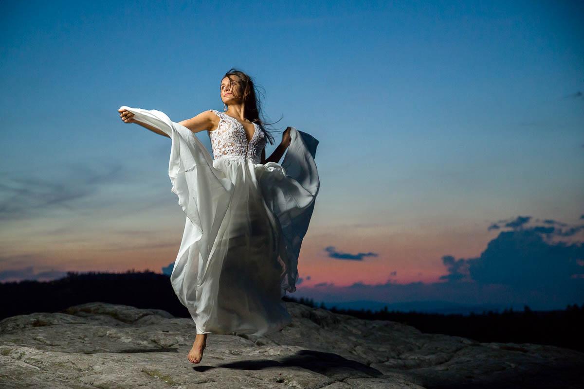 Panna Młoda w prostej sukni ślubnej unosi się jak anioł nad skałami na tle zachodzącego słońca