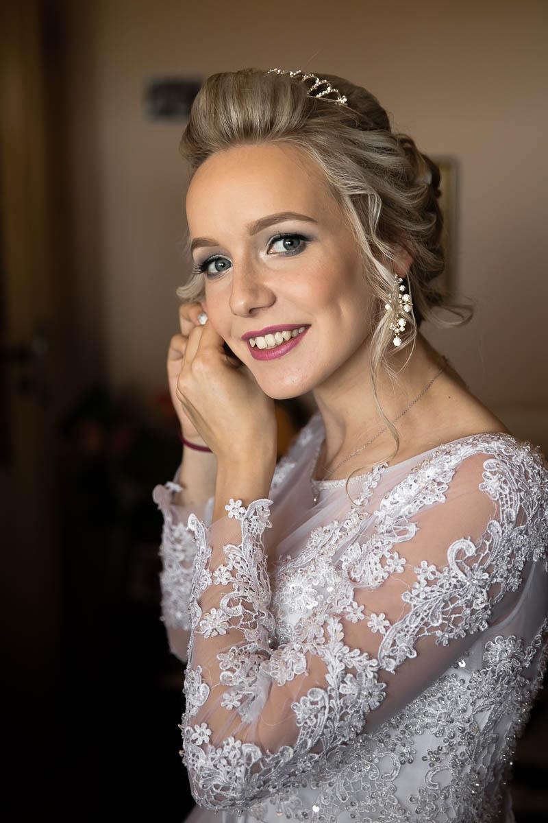 Uśmiechnięta Panna Młoda w koronkowej sukni ślubnej z długim rękawem zakłada kolczyk