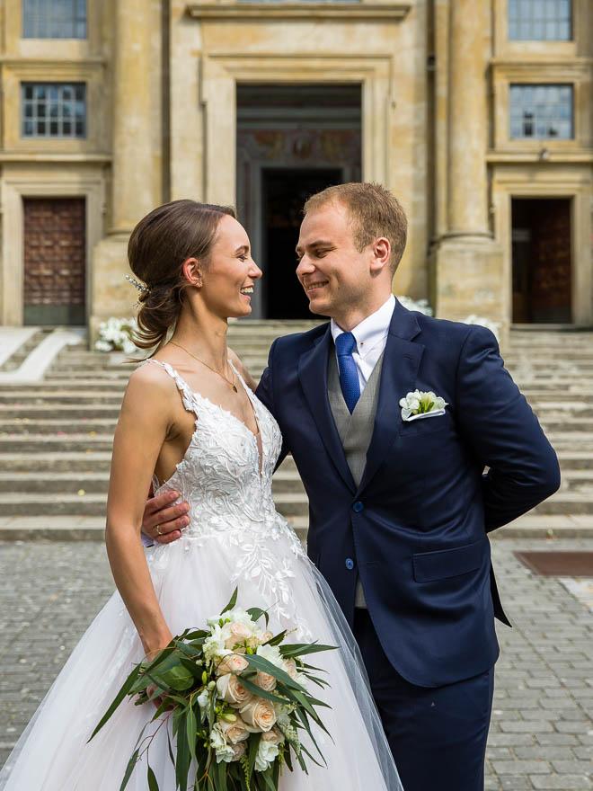 Pani Młoda w sukni ozdobionej koronką z bukietem ślubnym roześmiana z Panem Młodym po wyjściu z kościoła