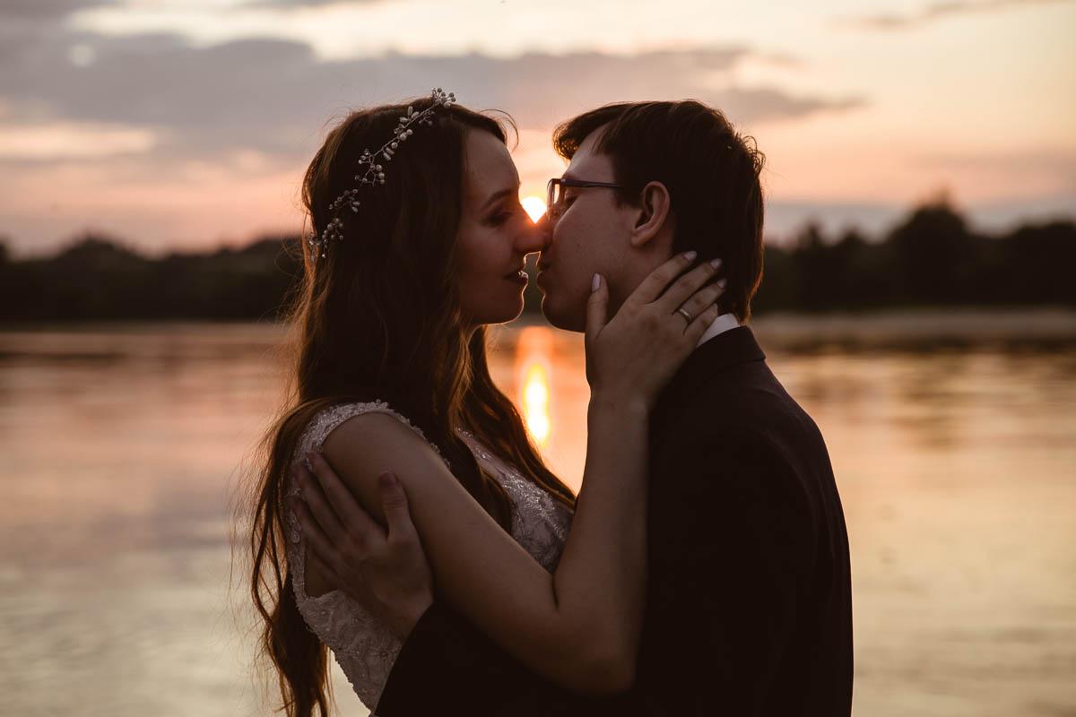 Para Młoda i czuły pocałunek nad Wisłą na tle zachodzącego słońca