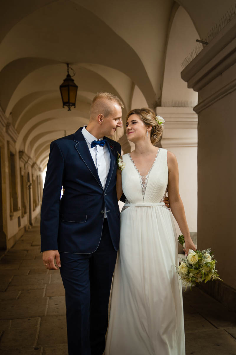 Pani Młoda w prostej sukni ślubnej spaceruje z Panem Młodym w podcieniach Rynku Wielkigo w Zamościu