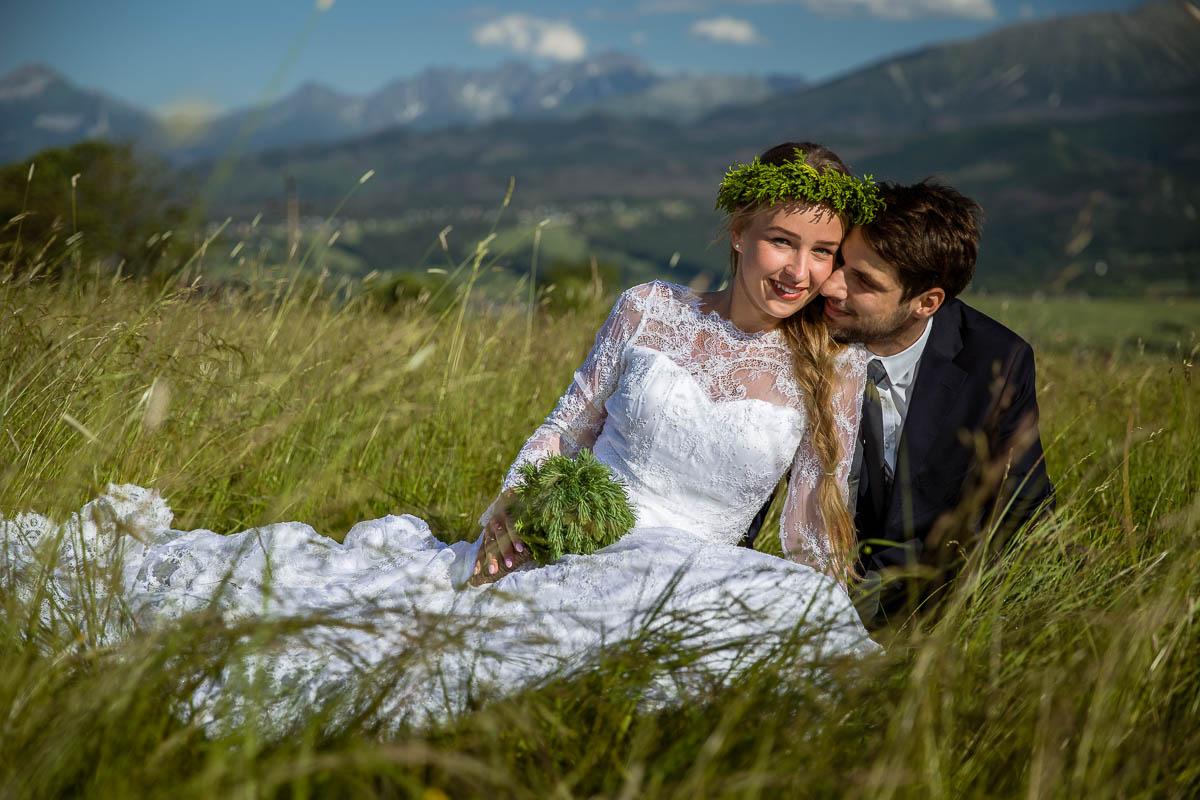 Panna Młoda siedzi na łące w sukni ślubnej z długim rękawem i wianku oparta o Pana młodego na tle gór