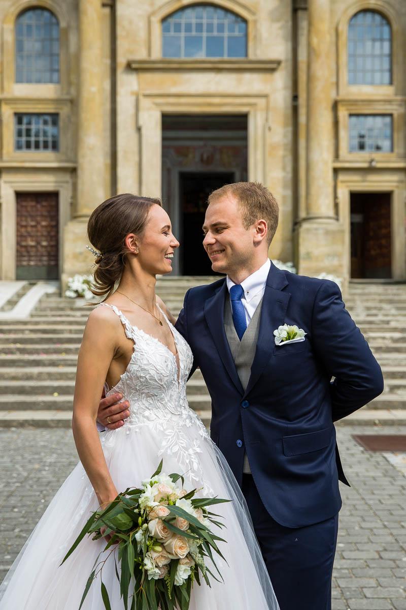 Młodzi po ślubie stoją szczęśliwi przed kościołem