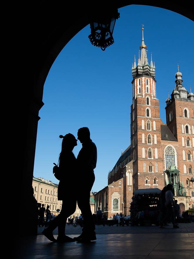 Narzeczeni na tle błękitnego nieba i Bazyliki Mariackiej w Krakowie