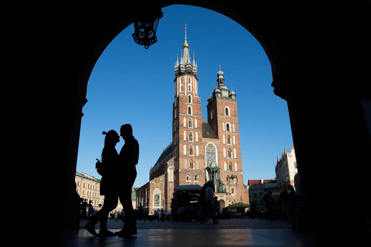 Sylwetki narzeczonych na tle błekitnego nieba i Bazyliki Mariackiej na Rynku Głównym w Krakowie