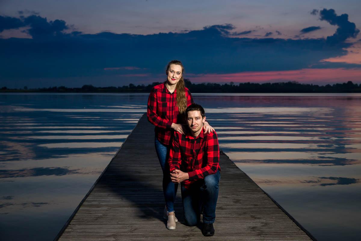Narzeczeni stoją na pomoście na jeziorze na tle zachodzącego słońca