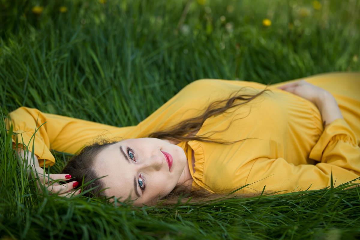 Dziewczyna z pięknymi oczami i w żółtej sukience leży w trawie